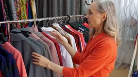 Gray haired elderly woman choosing dress in fashionable clothing store. Elegant woman choosing clothes in new fashion. Collection in showroom. Female shopping stock footage