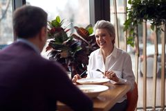 Gray haired elegant lady meeting with man in cafe. Enjoyable meetings. Waist up portrait of middle aged elegant smiling women communicating with mature male stock image