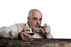 Gray-haired man with beard. A gray-haired man with a beard with a pipe and cognac Royalty Free Stock Photos