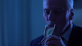Gray-haired man celebrating anniversary and drinking champagne, romantic date. Stock footage stock footage