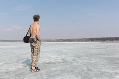 The gray-haired man with a naked torso standing on ice of the river Royalty Free Stock Photos