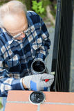 Gray-haired man painting modern metal gate Royalty Free Stock Images