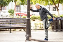 Mature man doing some leg stretches in the city royalty free stock images