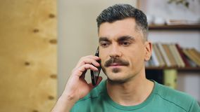 Gray-haired man talking on cellphone at home, making appointment with friends. Stock footage stock video