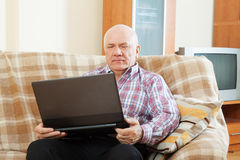 Gray-haired man working at his laptop Royalty Free Stock Photo