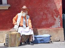 Gray-haired old man sits near his accordion. An accordion stands next to an old man with a cigarette. Old musician earns his