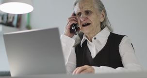 A gray-haired old woman works at a laptop and talks on a mobile phone. Business grandmother sitting in an office stock footage
