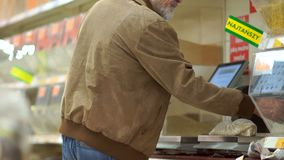 Gray-haired retiree with a beard weighs cereals on scales in a supermarket, sticks a price tag on a package. Lonely old. Man, grocery department stock footage