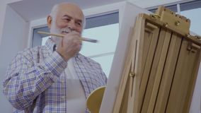 Gray-haired senior man draws picture on easel standing near the window. Senior man draws picture on an easel at home standing near the window. Elderly gray stock video footage