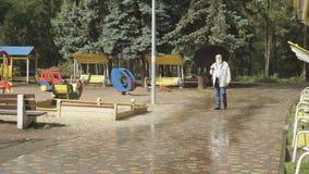 Gray-haired senior man walks with umbrella in rainy park. Senior man walks during the rain in park. Old man with black umbrella is walking alone in the autumn stock footage