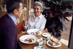 Gray haired smiling woman with cup of water in cafe. Enjoyable meetings. Waist up portrait of happy smiling gray haired lady with cup of water sitting in cafe stock photography