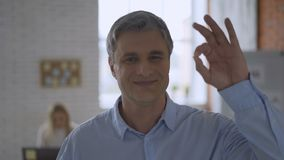 Gray-haired solid man shows gesture okay. top manager in the office 4K. Gray-haired solid man shows gesture okay. top manager in the office stock video