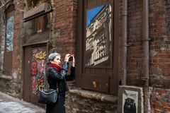 A gray haired woman take pictures of the decoration on an unnamed street near the Merchants Caffe in Seattle stock photos
