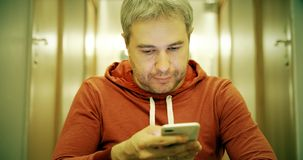Gray haired young man in casual clothes uses his smartphone in the hallway royalty free stock photos