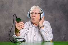 Gray hairy elderly woman listening music. With headphone Royalty Free Stock Photos