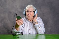 Gray hairy elderly woman listening music. With headphone Royalty Free Stock Photography