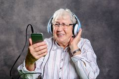 Gray hairy elderly woman listening music. With headphone Royalty Free Stock Photos