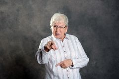 Gray hairy elderly woman pointing in to the camera. Gray hairy elderly woman looking angry and pointing in to the camera royalty free stock photography