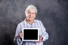 Gray hairy elderly woman using tablet pc. Gray hairy elderly woman showing tablet pc and looking amazed Stock Image