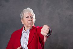 Gray hairy elderly woman showing thumb down. Gray hairy elderly woman looking angry and showing thumb down royalty free stock photos