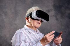 Gray hairy elderly woman using virtual reality glasses. And looking surprised Royalty Free Stock Images