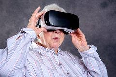 Gray hairy elderly woman using virtual reality glasses. And looking surprised Royalty Free Stock Photos