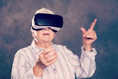 Gray hairy elderly woman using virtual reality glasses. And looking surprised Royalty Free Stock Photography