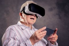 Gray hairy elderly woman using virtual reality glasses. And looking surprised Stock Image