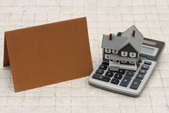 A gray house, brown card and calculator on stone background. With copy space for your message royalty free stock photo
