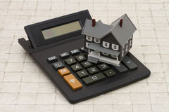 A gray house and calculator on stone background Stock Images