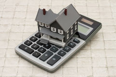 A gray house and calculator on stone background Stock Photos