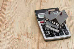 A gray house and calculator on wood background Royalty Free Stock Image