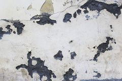 gray house of paint and old dirty plaster with cracks royalty free stock photography