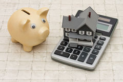 A gray house, piggy bank and calculator on stone background Stock Image