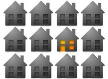 Gray houses, one with light Stock Photography