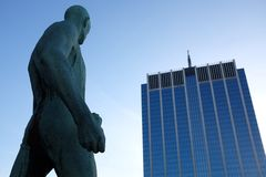 Gray Human Sculpture Near Blue Building During Daytime Royalty Free Stock Photos
