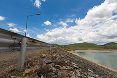 The gray iron barrier on the side of reservoir with mountain and beautiful clouds with green water and street lamps Royalty Free Stock Photo