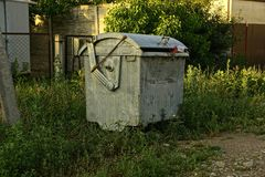 Gray iron trash can outdoors on green grass Royalty Free Stock Photography