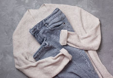 Gray jeans,   beige cardigan Stock Images