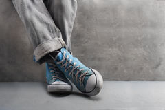 Gray jeans with nice sneakers on  concrete background Royalty Free Stock Photos