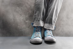 Gray jeans with nice sneakers on  concrete background Stock Photography