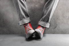 Gray jeans with nice sneakers on  concrete background Stock Photo