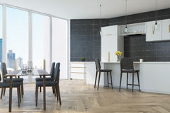 Gray kitchen with a table. Gray tiled kitchen with panoramic windows, a wooden floor, a dining table with blue chairs and white countertops and consoles. 3d Stock Images