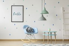 Gray knot cushion on a blue rocking chair standing in a white ch. Ild room interior with blue raindrops wallpaper on the wall. Real photo royalty free stock photo