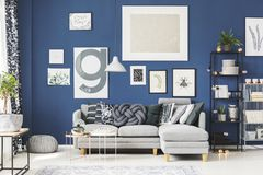 Gray knot cushion on sofa. Gray knot cushion lying on a gray corner sofa in bright living room with metal coffee tables stock image