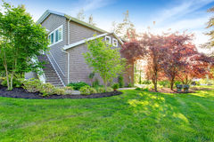 Gray large house exterior with green back yard and well kept lawn. Stock Photo