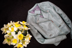 Gray leather jacket and a bouquet of daffodils. Black background. Fashionable concept Stock Photo