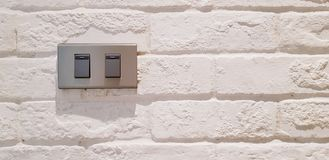 Gray light switch button installed on white rough or vintage wall royalty free stock photos