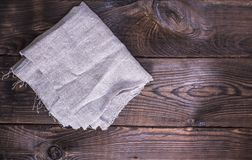 Gray linen napkin on a brown wooden background Royalty Free Stock Image
