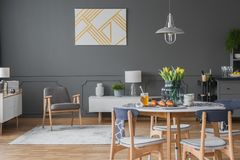 Gray living and dining area. Elegant, white and golden artwork and a modern armchair in a monochromatic open space apartment interior with living and dining area Stock Photography